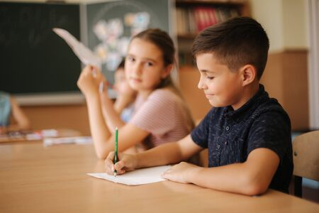 Group of school kids with pens and notebooks writing test in classroom. education, elementary school, learning and people concept