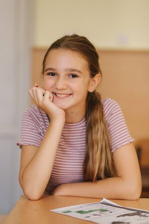 Happy schoolgirl sitting at desk and writing in exercise book Фото со стока