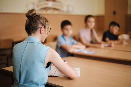 Female teacher in front of children. Pretty teacher in classroom sitting at the desk and asking children. education, elementary school, learning and people concept