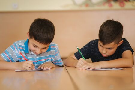 Two schoolboys writing text. Happy children in school