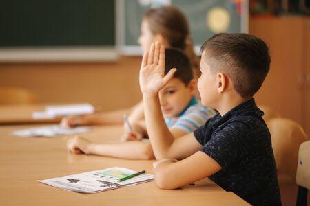Schoolboy rise hand in classroom. Elementary school. Education Фото со стока
