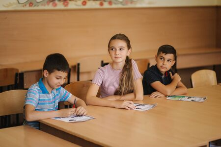Education, elementary school. Learning and people concept - group of school kids with pens and notebooks writing test in classroom