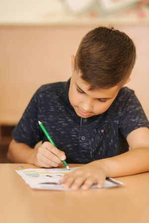 Concentrated schoolboy sitting at desk and writing in exercise book