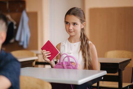 Schoolgirl take a notebook and write down homework