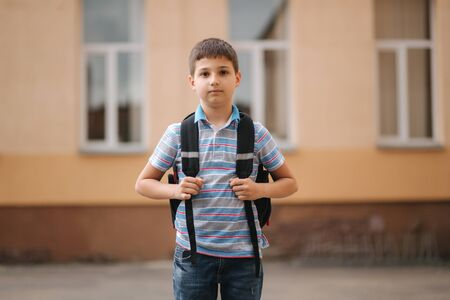 Cute little boy with backpack go home after scholl class