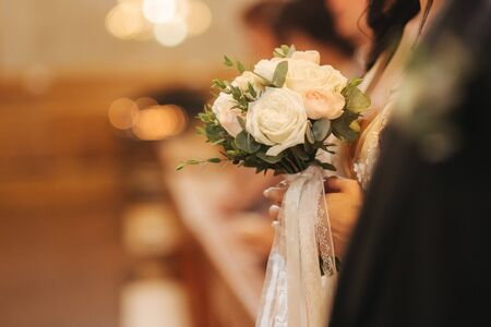 Element of decor in the church. Wedding bouquet in hands