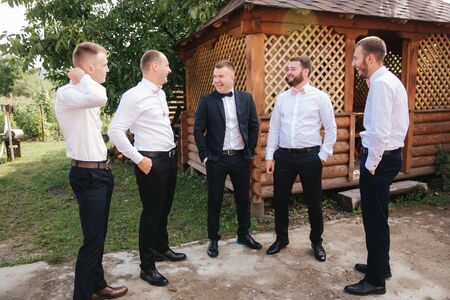 Handsome groom with his groomsman on the backyard. Five man. Groom dressed in suit, gromsmen in white shirt. Funny guys on the wedding