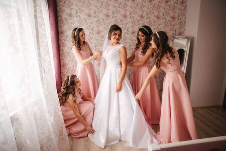 Gridesmaids help bride at her home. Morning of beaufiful bride. Girls hepl bride look wonderful Standard-Bild