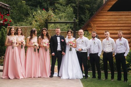 Groom and bride stand with groomsman and bridesmaid outside. Newlyweds kissing and friend clap. Wedding day Stock Photo