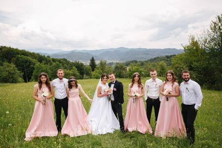 Groom and bride stand with groomsman and bridesmaid. Newlyweds kissing with friends. Wedding day. Background of mountsins Stock Photo