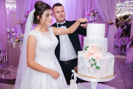 groom and bride in the restaurant stand by their wedding cake