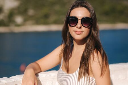 Portrait of young attractive woman in white clothes and sunglasses in front of beautiful sea. Vocation concept Imagens - 127819276