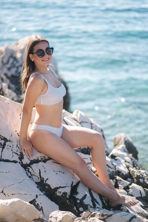 Woman sunbathing on the rock by the sea. Female in swimsuit and sunglasses on the vocation