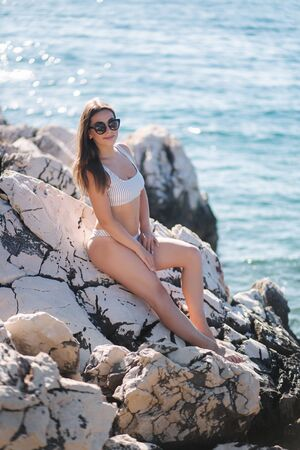 Woman sunbathing on the rock by the sea. Female in swimsuit and sunglasses on the vocation Imagens - 127819237