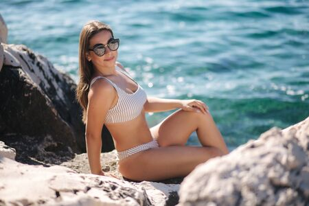 Sexy woman in sunbathing and enjoying summer sun on the rock. Woman on sea background. Relax on vocation Imagens