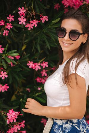 Gorgeous woman in sunglasses stand in beautiful flowers. Portrait of happy smiled young woman Stock Photo