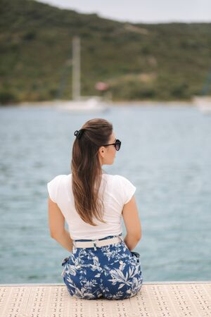 Back view of woman sit on the pier by the sea. Beautiful sea