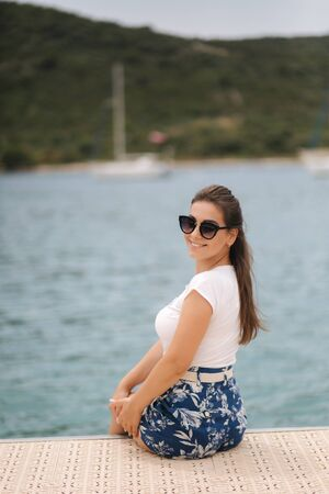 Attractive stylish woman on the pier by the sea. Beautiful inflow surrounded by mountains