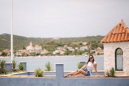 Fashion model in blue shorts and white shirt posing for photographer in beautiful inflow. Stylish woman in sunglasses