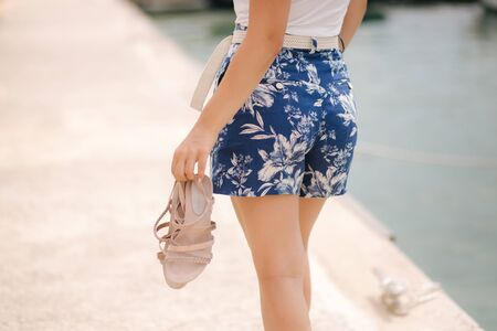 Young woman walking barefoot along the embankment. She hold shoes in hands. Mid selection. Back view Stock Photo