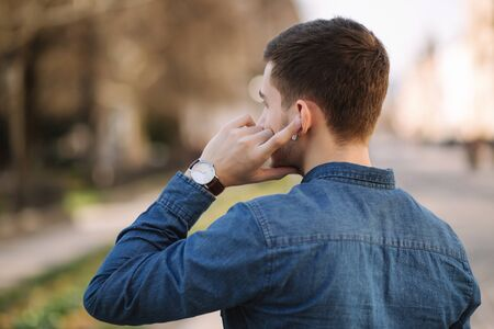 Handsome man put his finger on wireless headphones and speaks. Portrait of man makes conversation by the phone