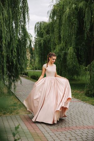 Fashionable girl spin around in park. Evening dress