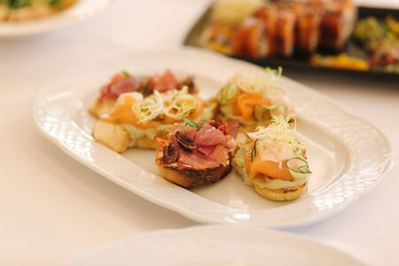 Appetizer in restaurant. Banquet concept. Bruschette with salmin and ham, decorated with basil and chile Zdjęcie Seryjne