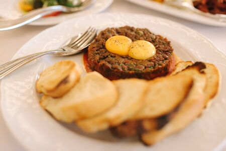Beef tartare with eggs yolks and toasts. Banquet concept