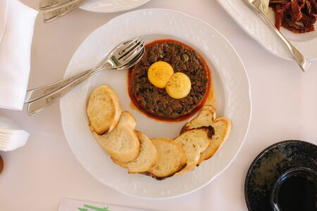 Beef tartare with eggs yolks and toasts. Banquet concept. top view