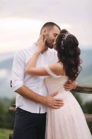 Charming bride hug her handsome groom in mountains. Beautiful wedding couple walk. Green gackground