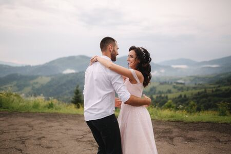 Beautiful wedding couple in Carpathian mountains. Handsome man with attractive woman. Bride spin around Stock Photo