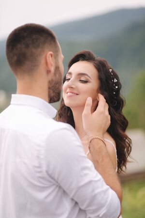 Close up portrait of beautiful couple in mountains. Happy woman with man. Elegant female with her husband