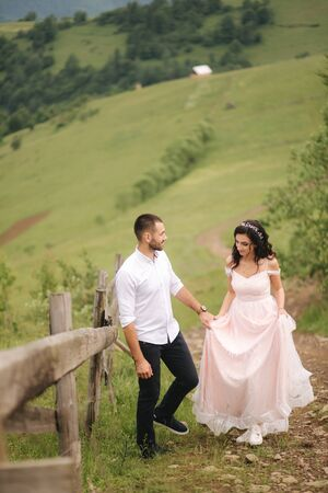 Beautiful young wedding couple standing on the green slope, hill. Groom and bride in Carpathian mountains Stock Photo