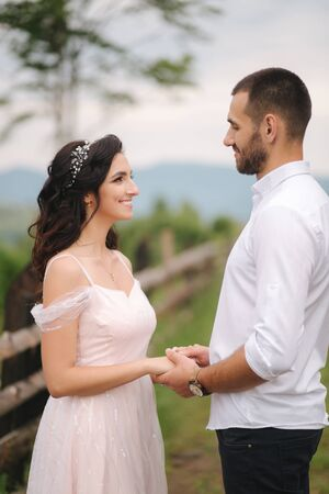 Lovestory of beautiful couple in the mountains, Handsome bearded man with beautiful and charming woman. Couple stand in front of beautiful tree