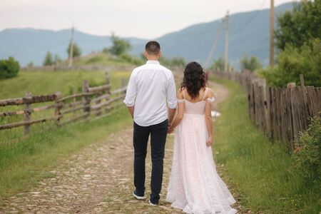 Handsome man leads his bride to beautiful Carpathian mountains. Happy wedding couple. Back view