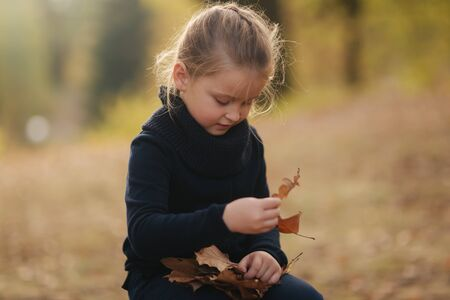 A little girl in black clothes is sitting on a stump and playing with autumn leaves. Blond hair girl Stock Photo