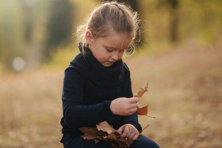 Una niña vestida de negro está sentada sobre un tocón y juega con las hojas de otoño. Chica de pelo rubio Foto de archivo