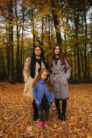 Mom and two daughter have fun in ther park. Youngest daughter collect leaves and smile. Happy family walking in the forest