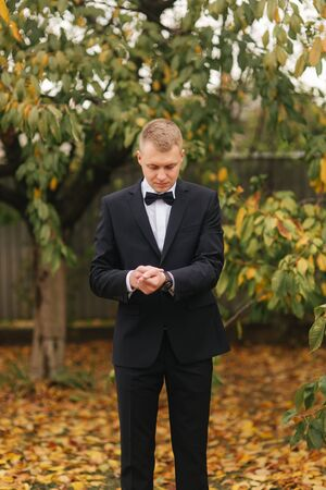 Handsome groom in wedding suit outside, autumn. background of yellow tree. Man in black suit with beautiful tie bow