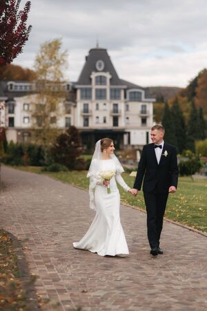 Stylish couple walking in the park at their wedding day. Happy newlyweds outside in autumn weather. Background of yellow and red leafs