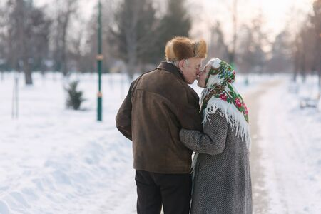 Back view of elderly couple walking in the park. Happy old people toghether though the years