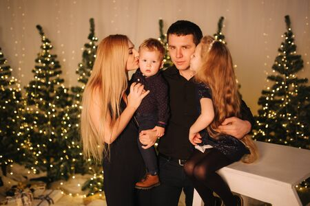 Christmas Family. Portrait of dad, mom, daughter and son sitting at home by the Christmas tree. Happy family. Christmas mood Stock Photo