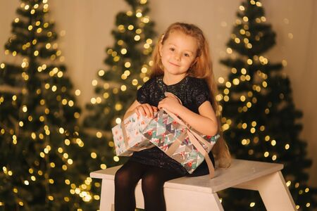 Little happy child sitting in front of Christmas trees. Blond hair female posing for photographer