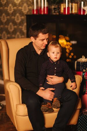 Handsome man with son sitting on the armchair at home. Christmas mood