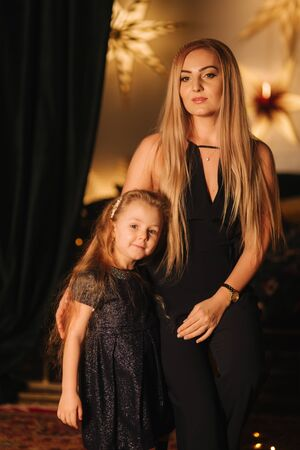 Beautiful blond hair mom with cute daughter in christmas time. Happy family