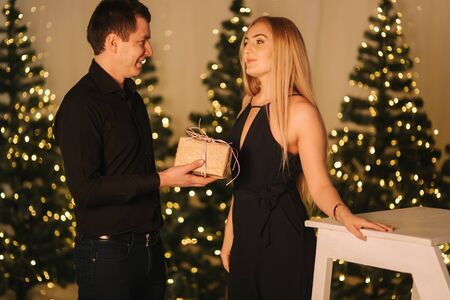 Husband gives present for his wife, background of Christmas trees. Happy woman take present
