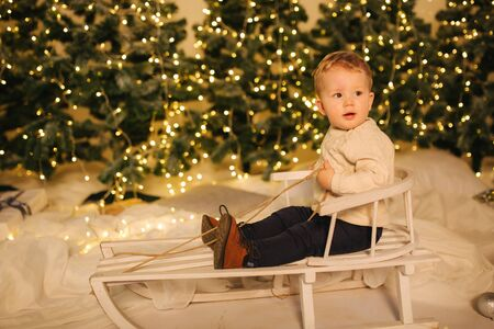 Little boy sitting on sleigh at home in front o Christmas trees. Winter holiday
