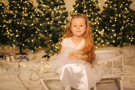Little girl sitting on sleigh at home in front o Christmas trees. Winter holiday Stock Photo