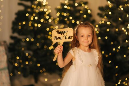 Cute little girl stand in front of Christmas trees and play. Winter holiday. Christmas mood
