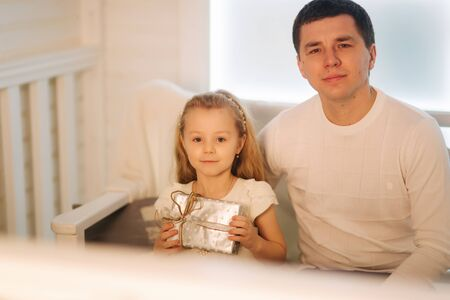 Father with daughter in Christmas time. Dad give a present for his little cure daughter Stock Photo